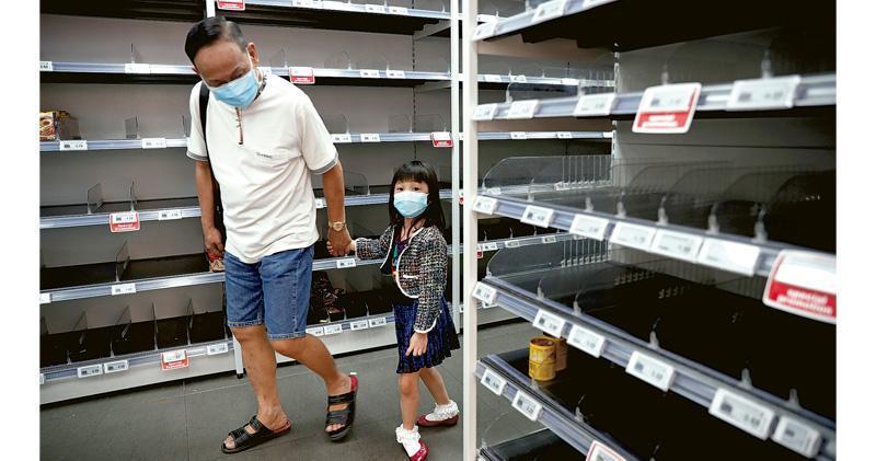 新加坡政府日前提升對武漢肺炎疫情的警戒級別後,大批市民連續兩日到超市搶購食糧及日用品,多個貨架被清空。(路透社)