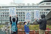 衛生署昨表示世界夢號郵輪的衛生檢疫工作已完成,全部乘客及船員可登岸,有市民拿着自製紙牌,一面是「屋企見」,背面是「撐住呀」,為船上乘客打氣。(馮凱鍵攝)