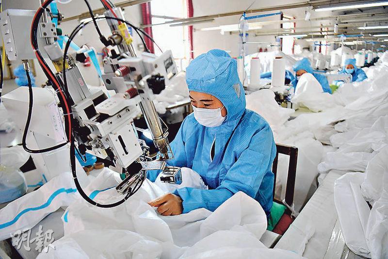 國務院聯防聯控機制表示醫用防護服仍是目前最緊缺的醫療物資。圖為2月12日,工人在山東寧津縣一家公司的車間內製作防護服。(新華社)