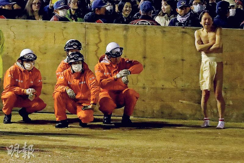 日本爆發武漢肺炎疫情下,地方仍繼續舉辦大型活動,例如岡山市的金陵山西大寺前天舉行「裸祭」,一名赤裸上身男子旁邊有救護人員穿著防護裝備戒備(圖)。熊本市昨日亦舉辦熊本城馬拉松,主辦當局向每名跑手和工作人員派發口罩。(路透社)
