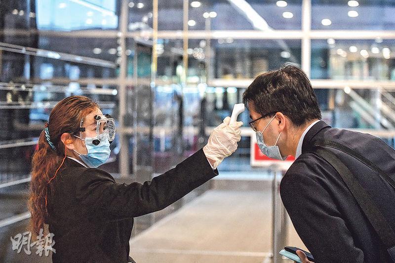 有員工確診新型冠狀病毒的巴馬丹拿集團的辦公室位於北角英皇道633號,該大廈昨有職員替進入大廈者探體溫。(鄧宗弘攝)