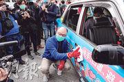的士及小巴業界昨日在中環舉行「的士小巴抗疫大行動」啟動禮,運輸及房屋局長陳帆(前)戴上口罩及手套,在傳媒面前拿起抹布清潔的士。(林若勤攝)