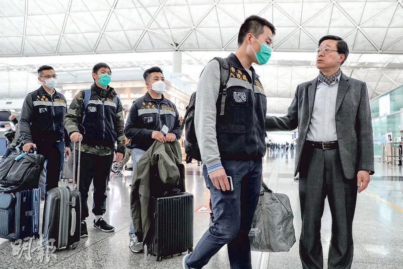 在日本橫濱停泊的鑽石公主號郵輪爆發新型冠狀病毒,350名香港乘客在船上接受隔離,周三隔離期將結束,港府昨派出由保安局、衛生署及入境處人員組成的先遣隊伍到當地協助,並派包機載港人回家。保安局長李家超(右一)昨到機場送行。(林若勤攝)