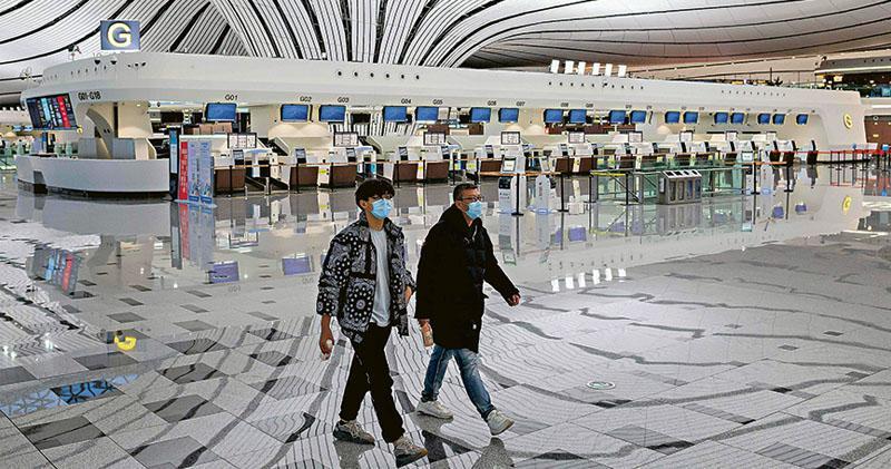 因新型冠狀病毒肺炎疫情影響,全國兩會料將推遲召開。圖為2月14日,兩名戴着口罩的男子走過北京大興國際機場空蕩蕩的航站樓;受疫情影響,大部分航班已經取消。(法新社)