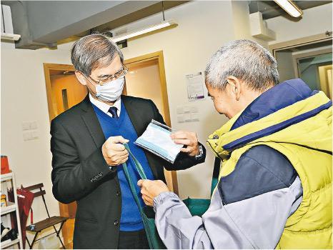勞福局長羅致光(左)前日戴住口罩落區,中止咗自己由大年初一開始無用過口罩嘅「紀錄」。(政府新聞處)