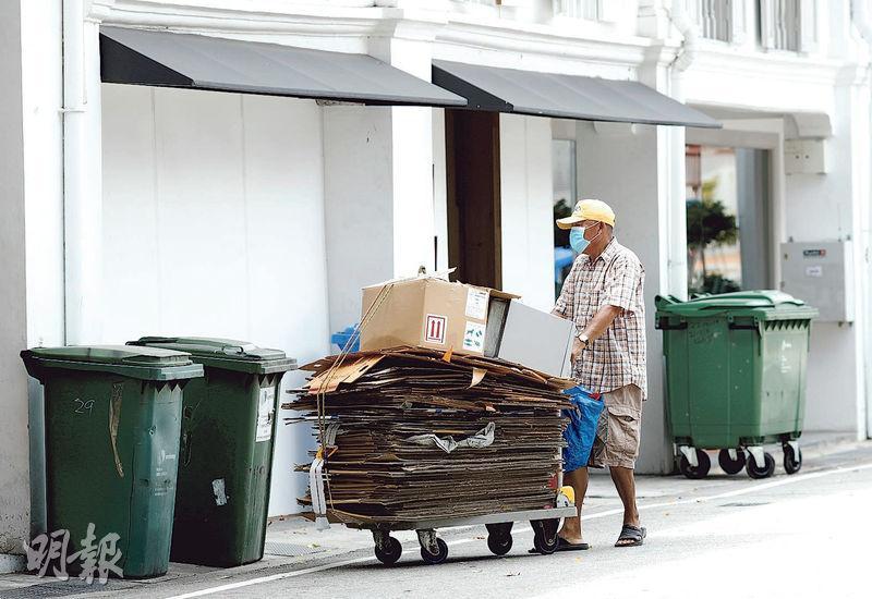 圖為一名戴着口罩的拾荒者昨在新加坡商業區撿拾紙皮。(路透社)