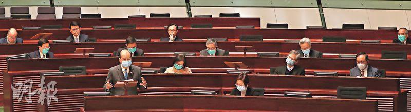 政務司長張建宗(站立者)昨與11名局長出席立法會緊急質詢。他回應議員提問時稱,若政府在防疫工作上做得不好,「希望市民包容」。12名司局長中,3人在立法會內無戴口罩。圖中前排右邊女士並非司局長。(李紹昌攝)
