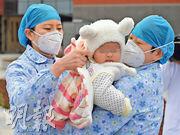醫務工作者昨日在江西省南昌市南昌大學第一附屬醫院治愈一名7個月大的新冠肺炎患者。這名嬰兒經過9天的治療後出院。(新華社)