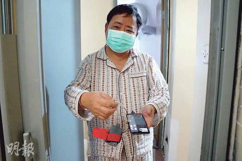 接受居家檢疫的吳伯(圖)說,衛生署人員曾為他戴上腳環(紅色帶裝置),但因不適已脫下,署方亦沒有反對。他說用右手腕的白色手帶,放置在狀似手機的機器「嘟」一下便完成定位,每日要「拍卡」3次報位置。(楊柏賢攝)