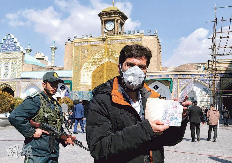 伊朗昨舉行國會選舉,德黑蘭市郊一名戴口罩的選民展示其證件。伊朗昨錄得13宗新型冠狀病毒感染個案。(法新社)
