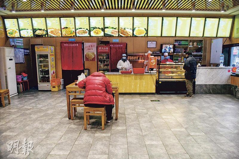 為應對復工,北京市應急管理局昨宣布,工業及信息企業辦公及住宿密度,人均面積不得小於2.5平方米,電梯只能讓滿載的半數搭乘。圖為2月20日,一名食客在只有一桌的北京餐館吃飯。(法新社)
