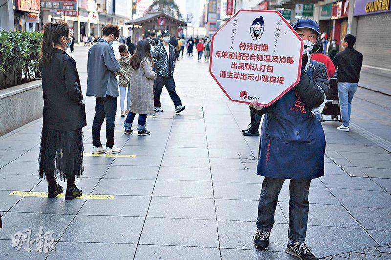 長沙一家網紅奶茶店復工,昨日工作人員舉起指示牌提醒顧客注意事項。(中新社)