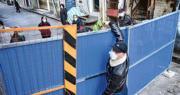 歷經一個多月「封城」,湖北武漢市昨日上午忽然宣布部分外地滯留人員可以出城,但出城令發布不足3個小時又宣告失效。圖為2月23日,武漢市一名男子從圍牆外向另一端的人傳遞蔬菜。(法新社)