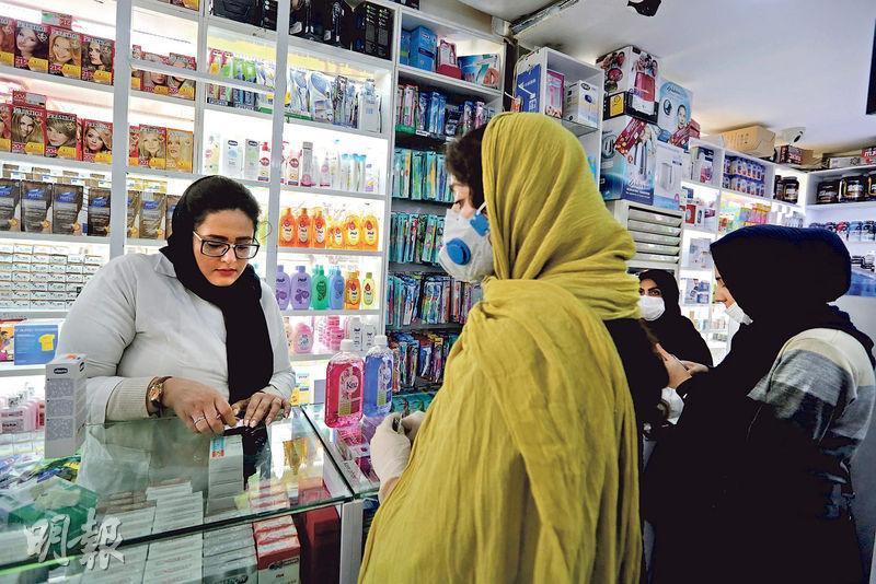 在伊朗首都德黑蘭,昨有戴口罩的婦女到藥房購物。(法新社)