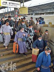 在大阪新幹線車站,周日一些準備參加相撲大賽的相撲手也戴上口罩。(法新社)