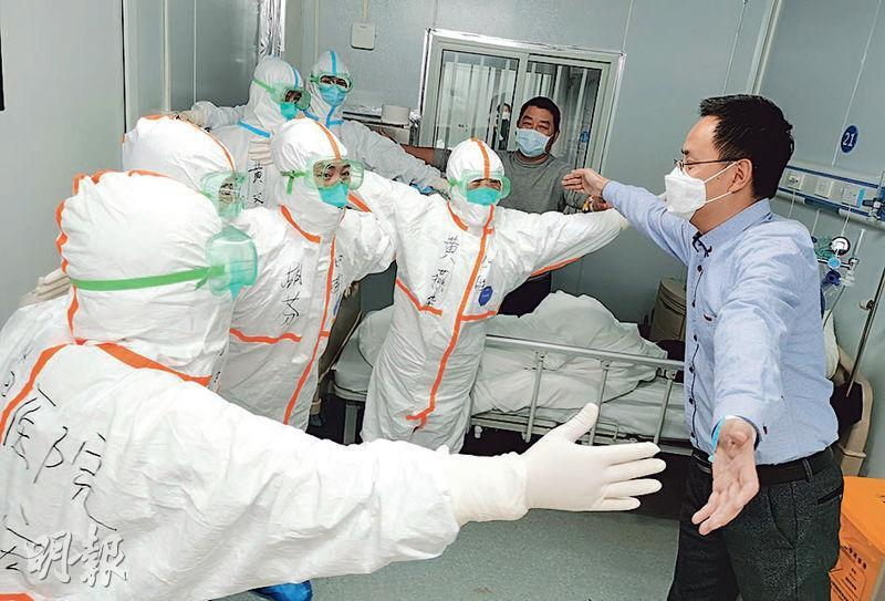 36歲的新型冠狀病毒肺炎康復者王先生,18日離開武漢雷神山醫院前,與醫護人員張開雙臂,以示「相擁」。(新華社)
