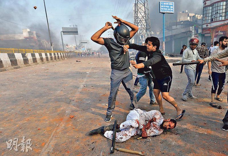 支持修例的民眾周一在新德里街頭毆打一名反對修例的穆斯林(倒地者)。(路透社)