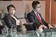 財政司長陳茂波的太太許步明(左)、兒子陳天行(右)噚日去立法會撐場聆聽預算案,疫情下兩母子隔個空位坐,保持距離。(曾憲宗攝)