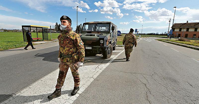 意大利北部市鎮圖拉諾洛迪賈諾被列為疫情嚴峻的「紅區」,昨日有戴上保護面罩的軍人駐守當地的出入口。(路透社)