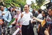 馬來西亞人民公正黨主席安華(中)周三在他的吉隆坡住所外舉行記者會,在他右邊的是他的妻子兼前副首相旺阿兹莎。(法新社)