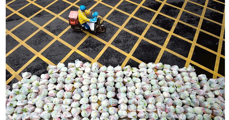武漢至今限制民眾外出,每日當局都會安排人員集中運送民眾當日所食用的蔬菜。圖為26日在街頭等待運送的一包包已分好的蔬菜。(法新社)