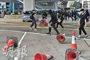 網上有人號召於筲箕灣遊行反對設武漢肺炎診所,其間有黑衣人在筲箕灣道用雪糕筒「快閃」堵路,防暴警及後到場戒備。(林若勤攝)