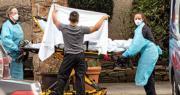 美國華盛頓州衛生防疫人員上周六從柯克蘭一間護理中心,移送疑似感染新型冠狀病毒的病人上救護車。(法新社)