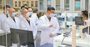 國家主席習近平(中)昨日在北京考察新冠肺炎防控科研攻關工作。這是習近平在軍事醫學研究院重大疫情應急防控藥物研究室了解疫苗和抗體研製情况。(新華社)