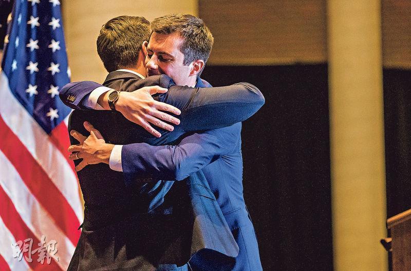 美國民主黨內提名參選人布蒂吉格(右)周日在其根據地南本德市宣布退出後,在台上擁抱他的丈夫。(路透社)