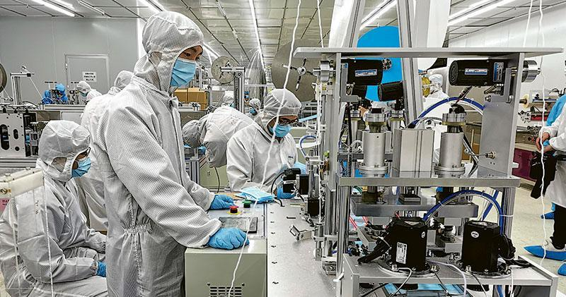 富士康科技集團在深圳龍華科技園新開的口罩生產線上,周一有工人開工。(新華社)