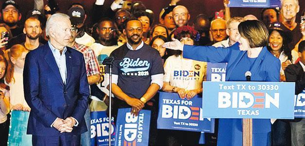 美國民主黨總統參選人拜登(前左)周一在達拉斯獲退選的克洛布徹(前右)上台發言支持。(路透社)