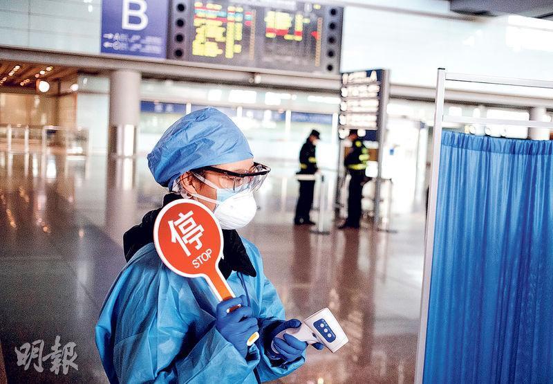 海關總署昨通報稱,截至前日內地海關一共檢出75宗新型冠狀病毒核酸檢測陽性病例。圖為一名戴兩層口罩、護目鏡、手套及身穿防護衣的檢疫人員,昨在北京首都機場入境大廳幫旅客測量體溫。(路透社)