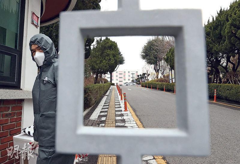 韓國政府衛生官員昨日進入有46人確診的大邱「疫廈」。這批患者全部都是新天地教會女信徒,當局仍在調查她們染病是與教會還是居所有關。(法新社)