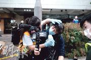 昨午警方在驅散示威者期間多次噴射胡椒噴霧,大批記者被噴中。圖中一名手持攝錄機的記者(右)被噴胡椒噴霧後,需由急救員(左)清洗眼睛。(馮凱鍵攝)