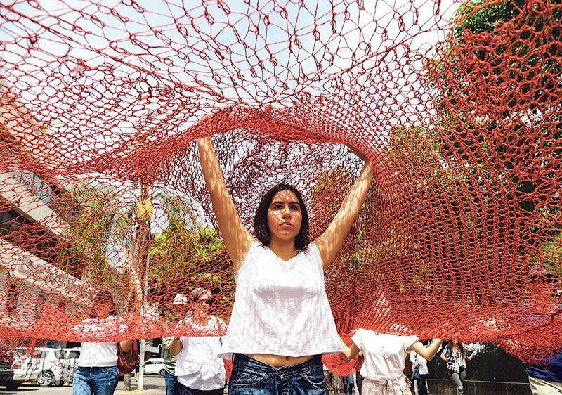 在墨西哥城市瓜達拉哈拉(Guadalajara),前天有婦女高舉象徵鮮血的巨型紅色圍網遊行,要求為被殺害的婦女討回公道。(路透社)