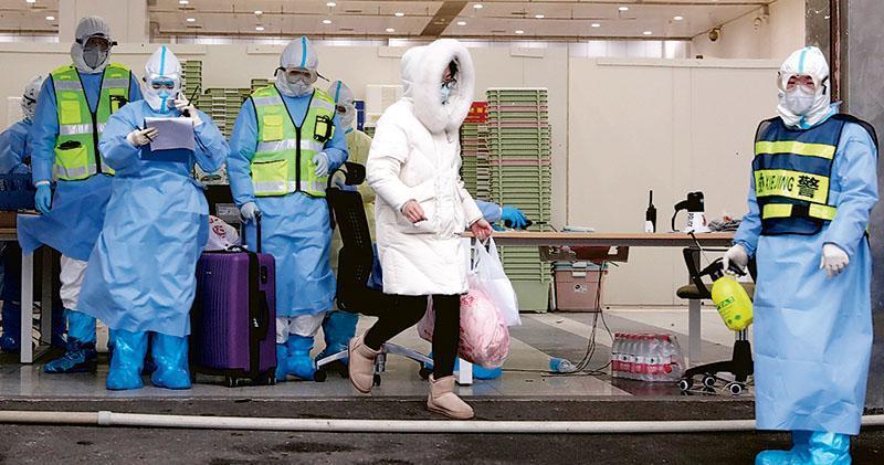 新冠肺炎疫情最高峰時,武漢有16家方艙醫院運行,目前,只剩武昌方艙醫院、江夏方艙醫院。圖為昨日江漢方艙醫院休艙時,院方認定的最後一名出院患者郭女士(右二)走出醫院。(新華社)