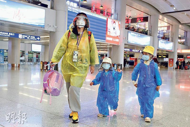 內地的新冠疫情有所緩解,但局勢仍未緩和。圖為昨日戴着口罩和雨衣的乘客穿過北京首都國際機場幾乎空蕩蕩的候機廳。(路透社)