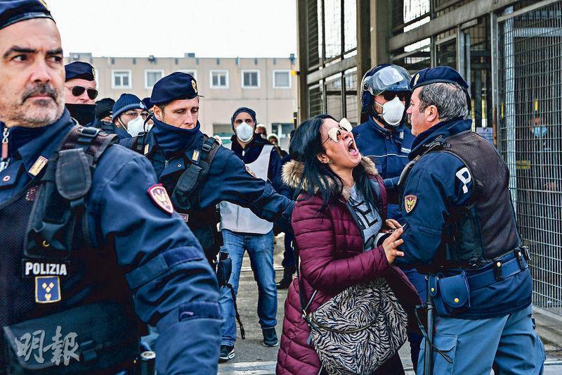 意大利摩德納一座監獄新訂限制囚犯會晤家屬的控疫措施後,監獄外昨有囚犯家屬叫喊抗議,警員在場維持秩序。(法新社)
