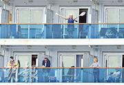 「至尊公主」號旅客周日在自己的客艙露台消磨時間。加州州長宣布將按他們的居住地或國籍,安排他們往指定的美軍基地或乘包機回國。(法新社)