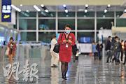 國泰有空姐確診新型冠狀病毒,為本港首宗同類個案。圖為一國泰空姐(紅衣者)在香港機場離境大堂戴着口罩。 (鄧宗弘攝)