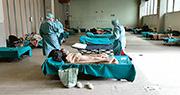 意大利醫療系統瀕崩潰,左圖為周五倫巴第地區布雷西亞一間醫院外搭建臨時緊急設施,收容懷疑患者,醫護為患者做病毒檢測。(法新社)