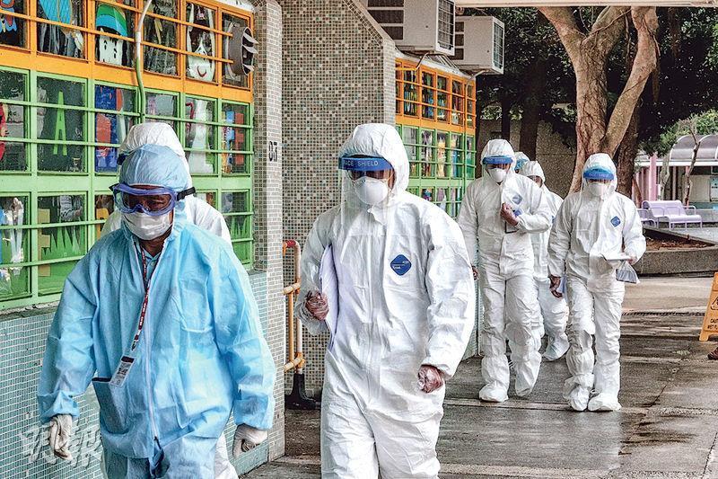 富亨邨亨泰樓接連有確診個案,昨早有穿上全套保護衣的政府人員進入調查,亦有清潔人員以稀釋漂白水清洗地下及大廈外牆。(曾憲宗攝)