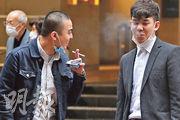《紐約時報》引述當地專家稱,病毒與吸煙時呼出的煙一樣,飄散一段距離後,病毒在空氣中的數量會非常低,認為公眾毋須過分恐慌。圖為兩名市民暫時脫下口罩抽煙聊天。(李紹昌攝)