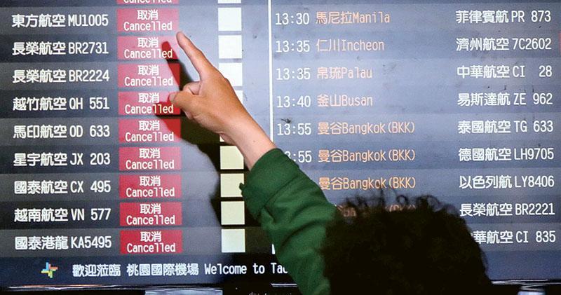 台灣境外輸入新冠肺炎確診病例昨日激增,政府宣布自今日起禁止非台籍人士入境。圖為昨日桃園國際機場的旅客在瀏覽航班信息,圖中多家外國航空公司已經取消航班。(路透社)