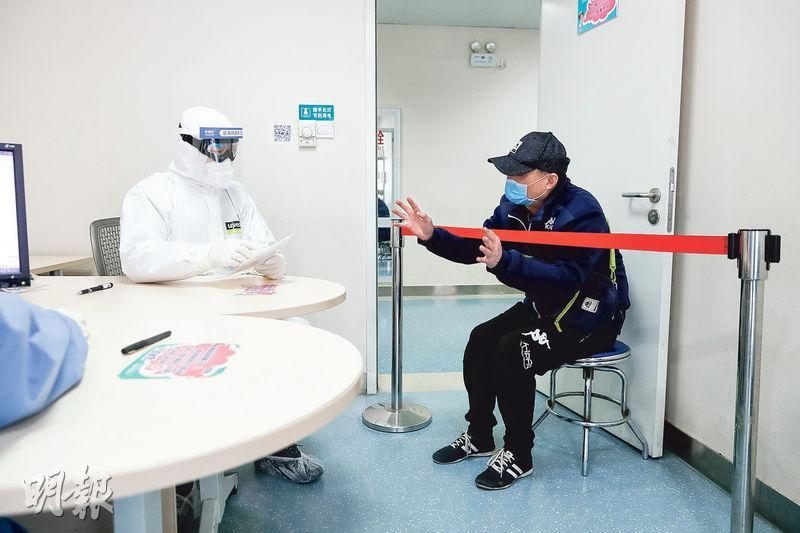 武漢市部分醫院近日開始為患有其他疾病的患者恢復治療,但卻發現一連多日有確診新冠肺炎患者來自門診,顯示防控疫情可能出現漏洞。圖為恢復接診的武漢協和醫院檢查一名患者,患者坐在紅線外。(新華社)