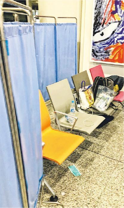 申報有病徵的入境者被安排到機場禁區等候送院;他們被分成數人一組等候,各小組以藍色布簾分隔。有份等候的Alvin稱,有人將口罩丟在地上,形容環境骯髒。(受訪者提供)