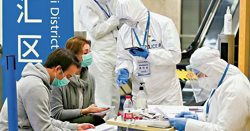 內地多個省市加強入境管控,嚴防疫情境外輸入。圖為3月18日,上海浦東國際機場的工作人員檢查抵境外籍旅客有關信息。(新華社)