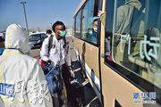 北京市日前啟用新國展作為首都機場入境旅客的轉運集散地。圖為3月17日,外籍的入境人員準備登上機場轉運車。(新華社)