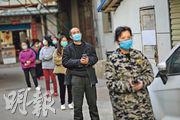 武漢昨首次通報單日無新增確診,市內無疫情小區開始部分解封。圖為前日當地居民排隊等候領取豬肉。(法新社)