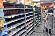 新冠肺炎疫情持續延燒,台灣的賣場出現搶購潮,昨日上午民生用品、罐頭等商品貨架上幾乎都被掃空。(中央社)